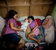 Fifi e suo figlio a casa a Giacarta. Spende la metà dello stipendio mensile del marito in latte artificiale. Fotografo: Poulomi Basu Fonte: The Guardian